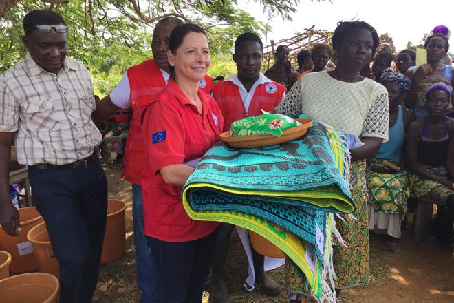 Foto: DRK-Mitarbeiterin verteilt Hilfsgüter an eine togolesische Frau