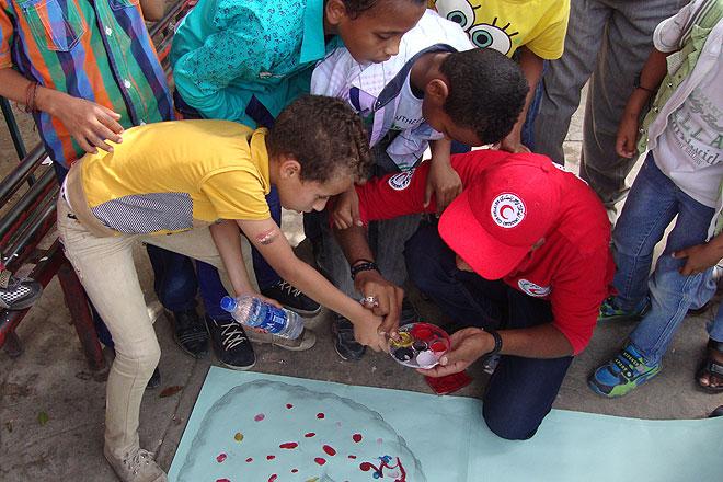 Ägyptische Schulkinder und ein Mitarbeiter des Ägyptischen Roten Halbmonds malen mit Fingerfarben