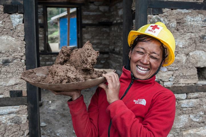 Foto: Eine nepalesische Rotkreuzmitarbeiterin hält lachend eine Schale Mörtel hoch.
