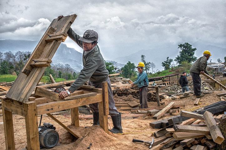 Erdbebenhilfe: Auf einer Baustelle sägt ein nepalesischer Bauarbeiter Holz mit einer elektrischen Säge.