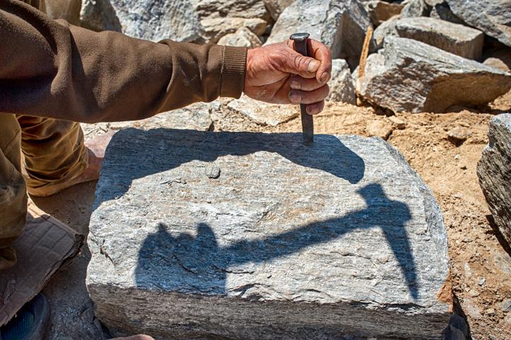 Foto: Ein Stein wird mit dem Meißel bearbeitet.