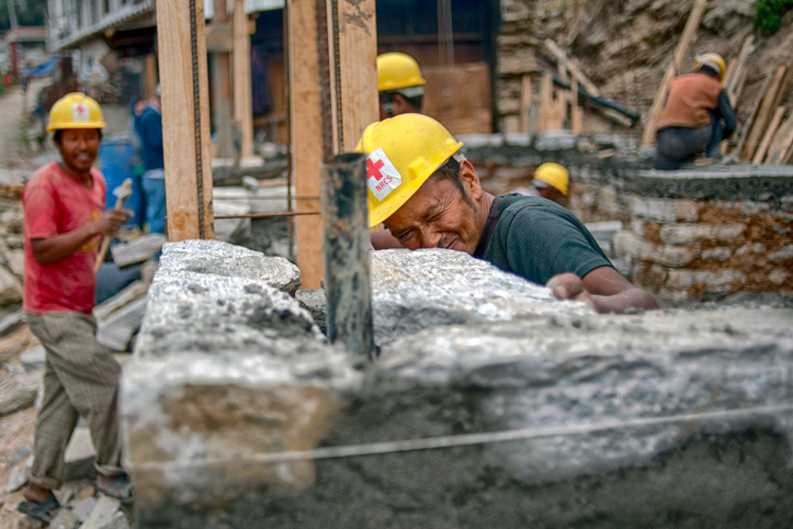 Foto: ein nepalesischer Rotkreuzmitarbeiter prüft die Ausrichtung einer Wand.