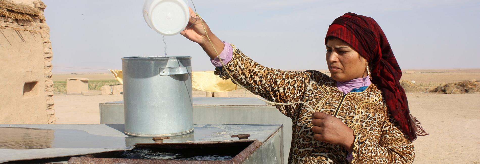 Foto: schwangere Syrerin schöpft Wasser aus einem Tank