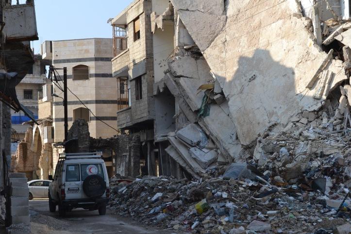 Autot vor zerstörtem Gebäude.
