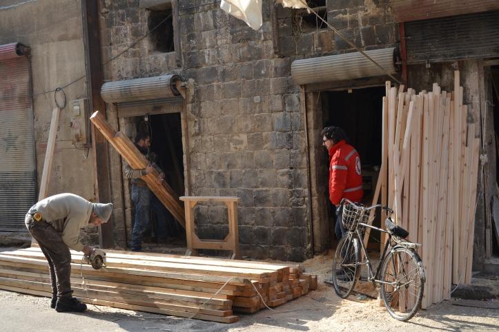 Schreinerarbeiten vor zerstörtem Haus.