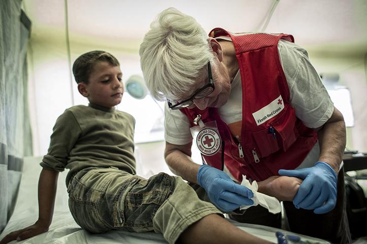 Foto: Finnische Rotkreuzhelferin behandelt das Bein eines Flüchtlingskindes.n in der Gesundheitsstation des Roten Kreuzes in Nea Kavala.