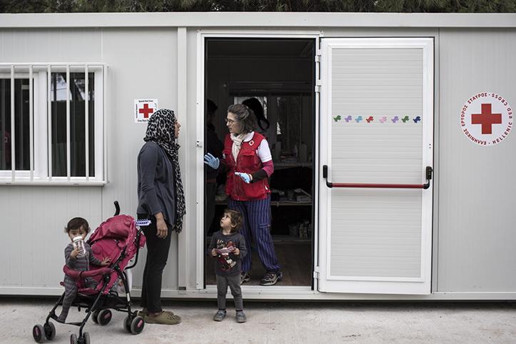 Foto: Eine geflüchtete Frau mit ihren Kindern in Gespräch mit einer Rotkreuzherlferin