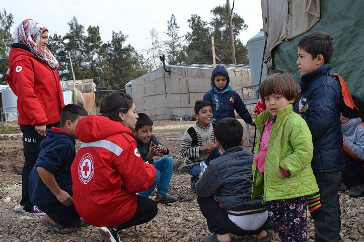 Mitarbeiter des Libanesischen Roten Kreuzes mit syrischen Flüchtlingskindern im Camp Zahrani.