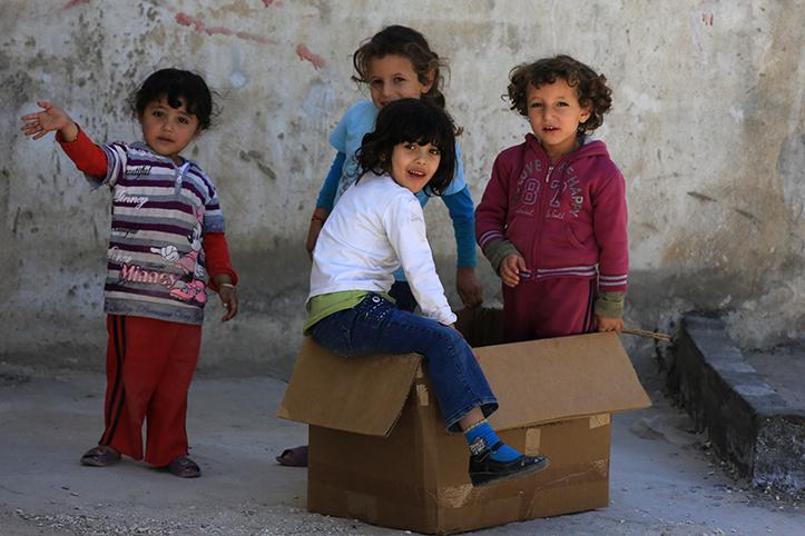 Foto: syrische Kinder spielen mit einem Karton auf der Straße