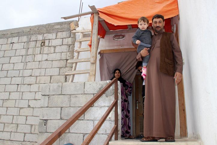 Foto: Ein geflüchteter syrischer Vater mit seinem Kind auf dem Arm vor seinem Haus