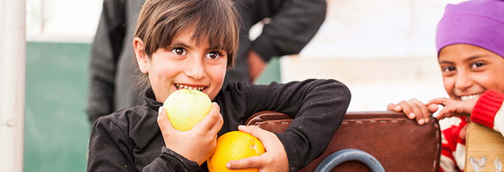 Foto: Ein geflüchtetes syrisches Mädchen freut sich über eine Orange und einen Apfel.