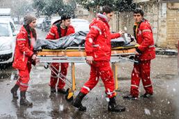 Foto: Sanitäter des Syrischen Arabischen Roten Halbmond tranportieren eine Person auf einer Trage