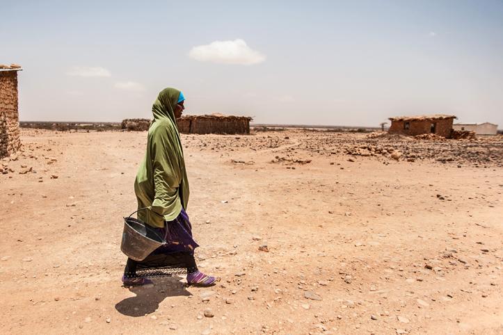Foto: Somalierin mit Eimer in trockenem Dorf