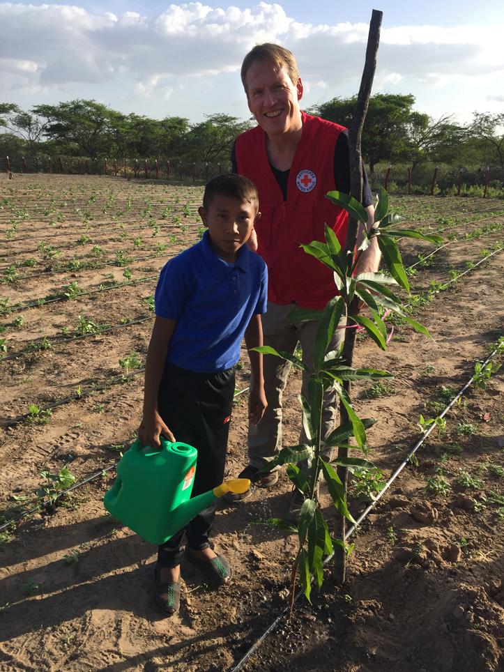Foto: Christian Reuter und ein kolumbianischer Junge gießen einen Baum.