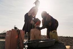 Foto: Zwei somalische Frauen schöpfen Wasser im Gegenlicht