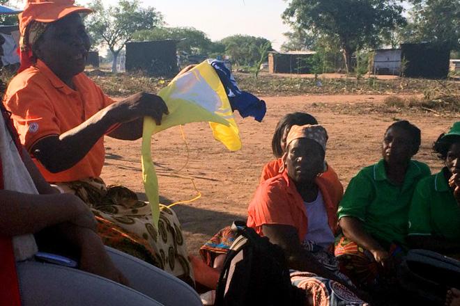 Foto: eine mosambikanische Frau zeigt anderen Frauen in einer Runde verschiedene Fahnen.