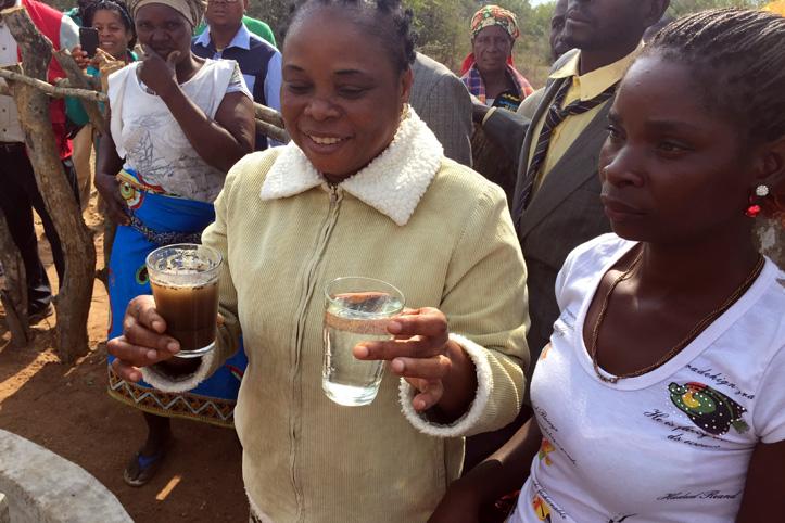 Foto: Mosambikanerin zeigt zwei Wassergläser - eines mit trübem und eines mit sauberem Wasser.