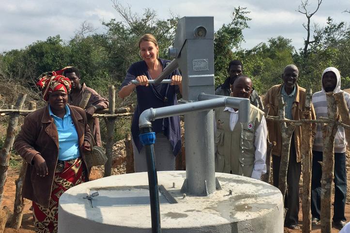 Foto: DRK-Mitarbeiterin und Dorfbewwohner in Mosambik nehmen neuen Brunnen in Betrieb