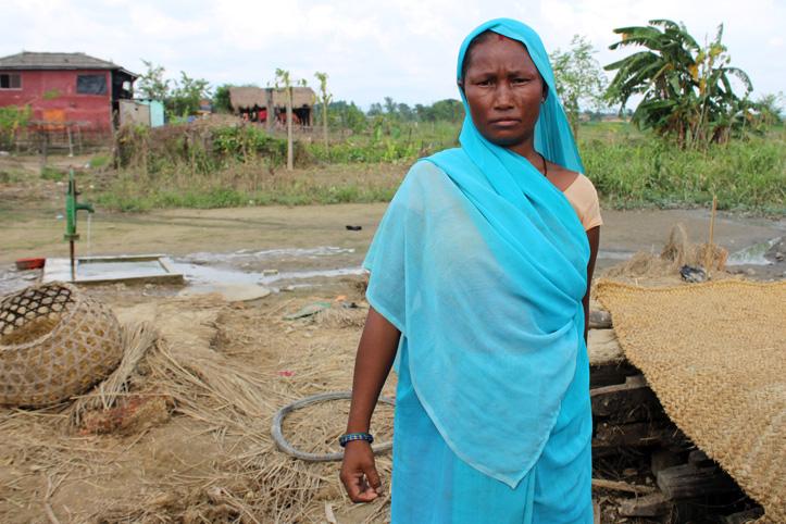 Foto: Nepalesin vor den Trümmern ihres Hauses.