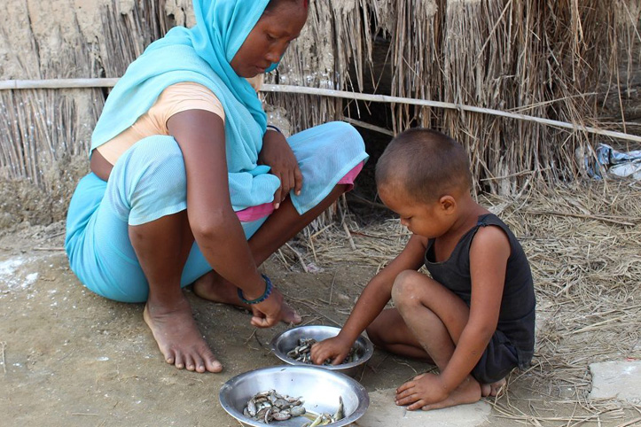 Foto: Nepalesische Mutter und ihr Sohn spielt vor Strohhütte mit Steinen.