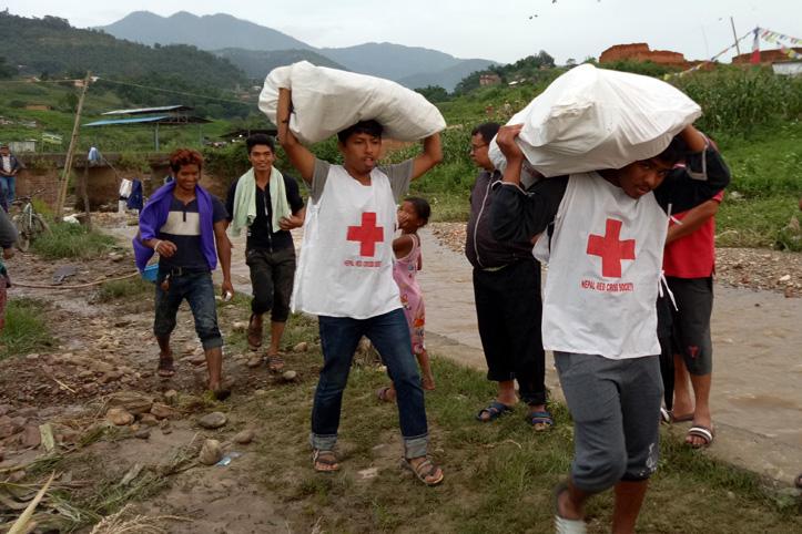 Foto: Nepalesische Rotkreuzhelfer tragen Hilfsgüter in unwegigem Gelände