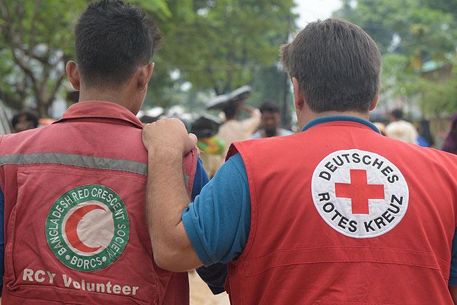 Foto: Mann mit DRK-Weste legt die Hand auf die Schulter von Mann mit BRH-Weste