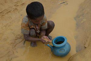 Foto: Kleiner Junge schöpft dreckiges Wasser in einen Krug