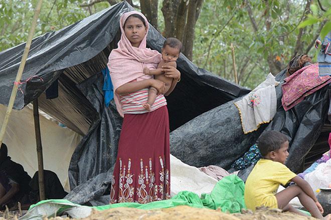 Foto: Eine junge Frau mit Kind auf dem Arm vor ihrem Zelt im Flüchtlingslager