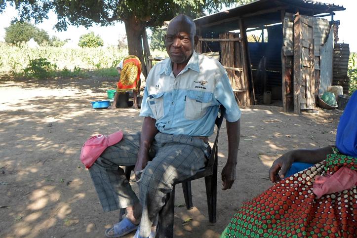 Foto: Älterer mosambikanischer Mann sitzt vor einer Hütte
