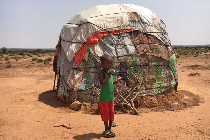 Foto. Junge vor eienr Hütte in der Steppe Somalilands