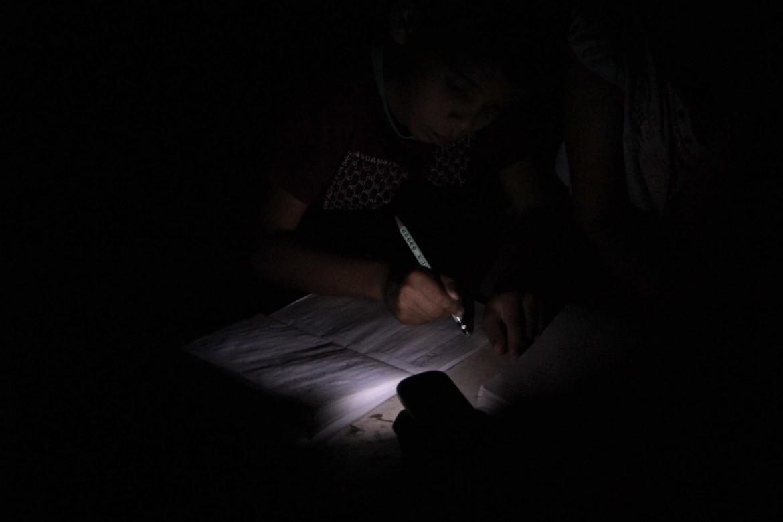 Foto: Kinder machen mit Taschenlampe im Dunkeln Hausaufgaben