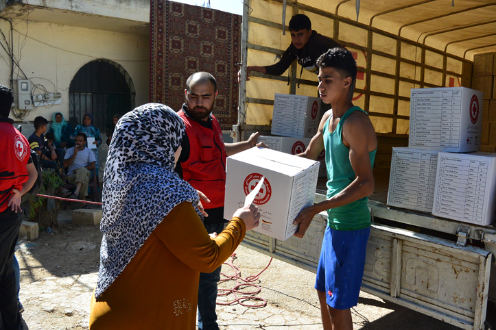 Foto: Rotkreuzmitarbeiter verteilen aus einem LKW heraus Hilfsgüter an Flüchtlinge