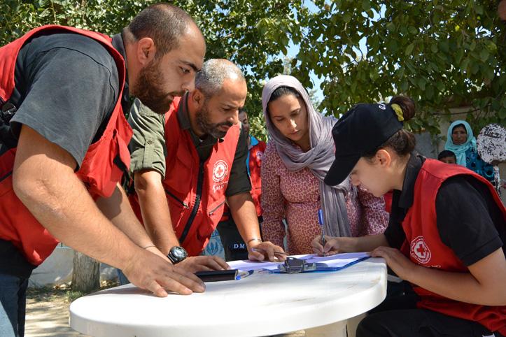 Foto: Rotkreuzhelfer und eine Schwangere bei der Abwicklung einer Hilfsverteilung