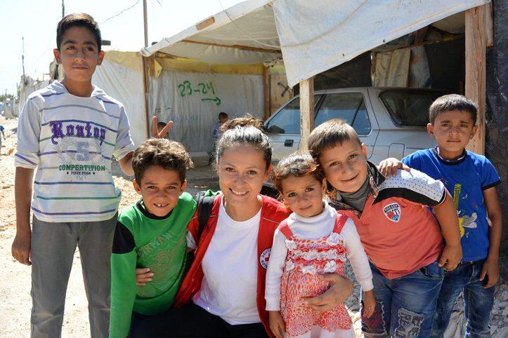 Foto: DRK-mitarbeiterin lacht mit syrischen Flüchtlingskindern in die Kamera