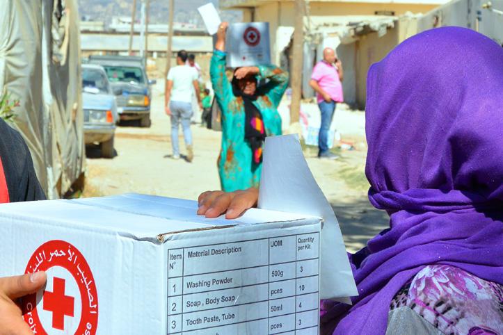 Foto: Straßenszene im Libanon - Frauen tragen Kartons mit Hilfsgütern