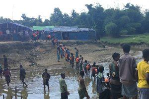 Flüchtlinge aus Rakhine tragen Hilfsgüter über einen Fluss in ein Lager
