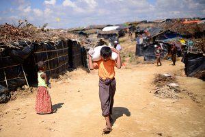 Eine Junge in einem Flüchtligslager in Cox's Batar trägt ein Hilfspaket