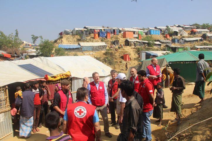 Gruppe von Rotkreuz-Mitarbeitern vor Hütten