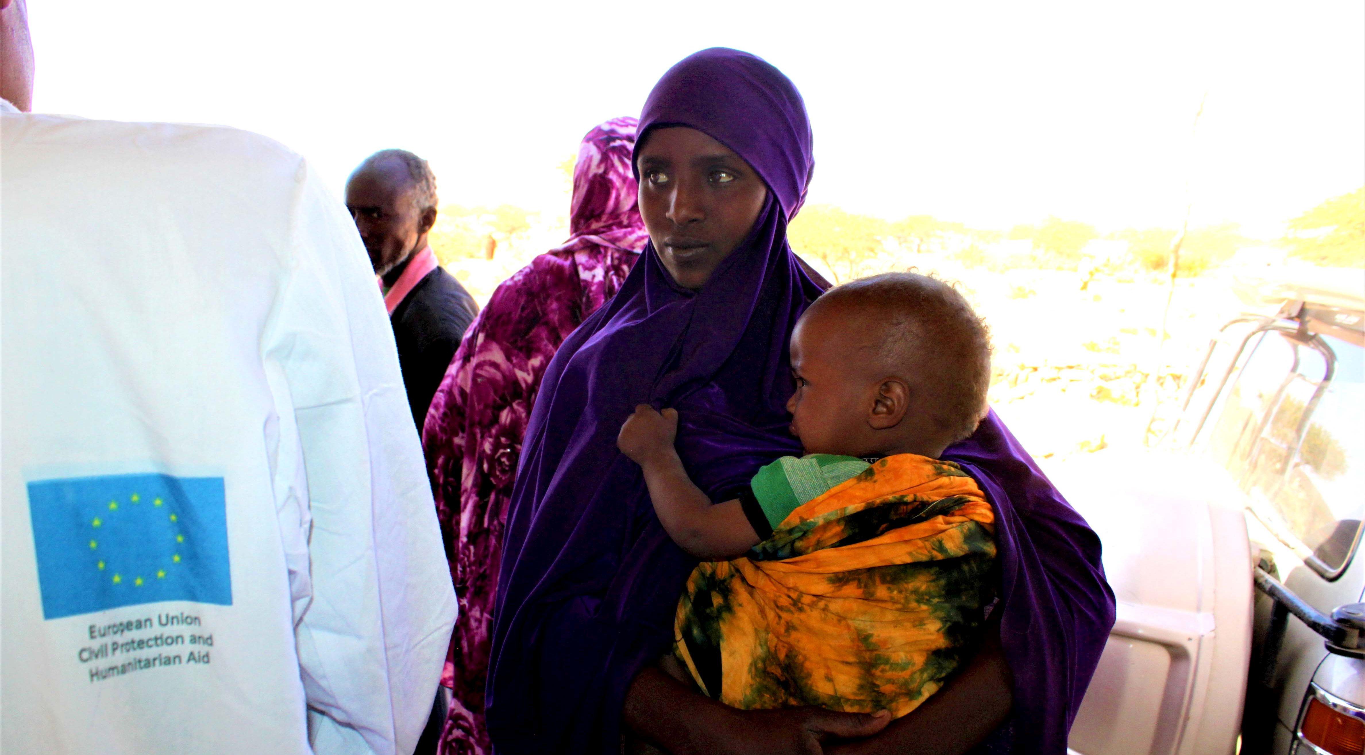 Junge Mutter mit Kind und Helfern