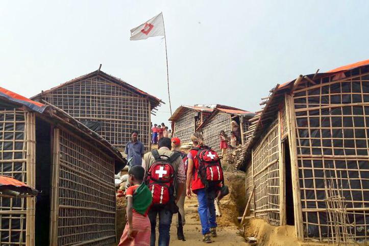 Foto: Rotkreutmitarbeiter auf dem Weg durch ein Flüchtlingscamp in Bangladesch