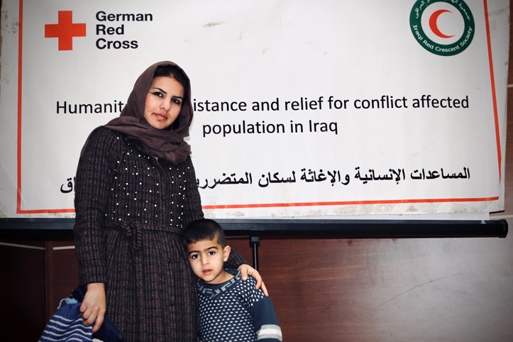 Foto: irakische mutter und ihr Sohn vor einem Info-Plakat