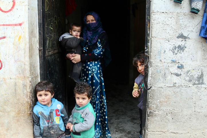 Foto: syrische Frau im Hauseingang mit ihren Kindern