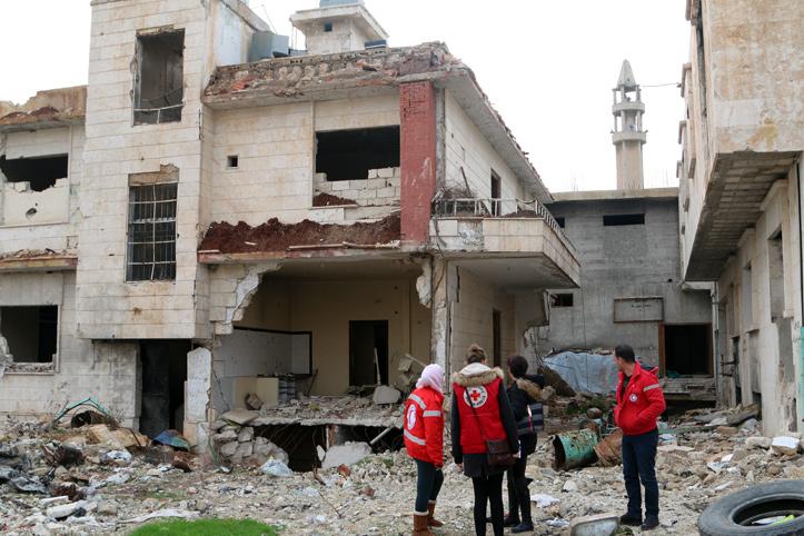 Foto: Helfer zwischen zerstörten Häusern in Syrien