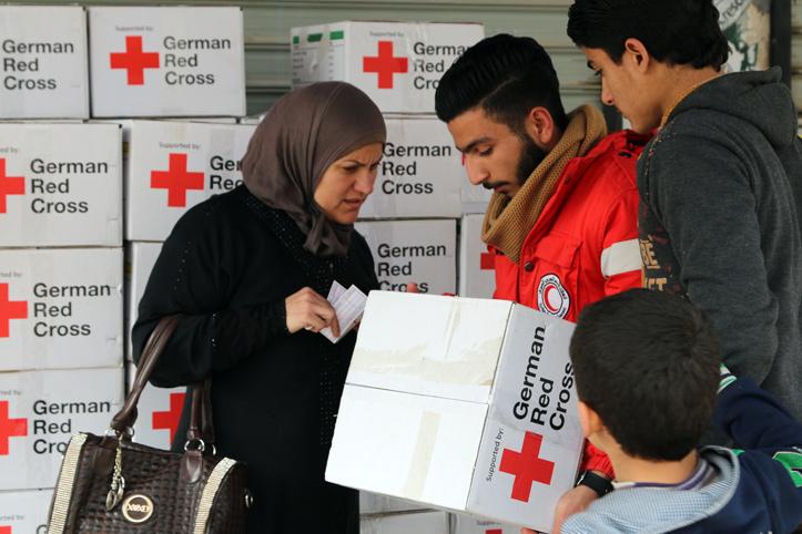 Foto: syrische Frau mit ihrem Sohn nimmt Karton mit Hilfegütern entgegen