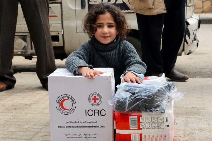 Foto: kleines syrisches Mädchen lehnt sich auf Rotkreuz-Hilfsgüter und lächelt.