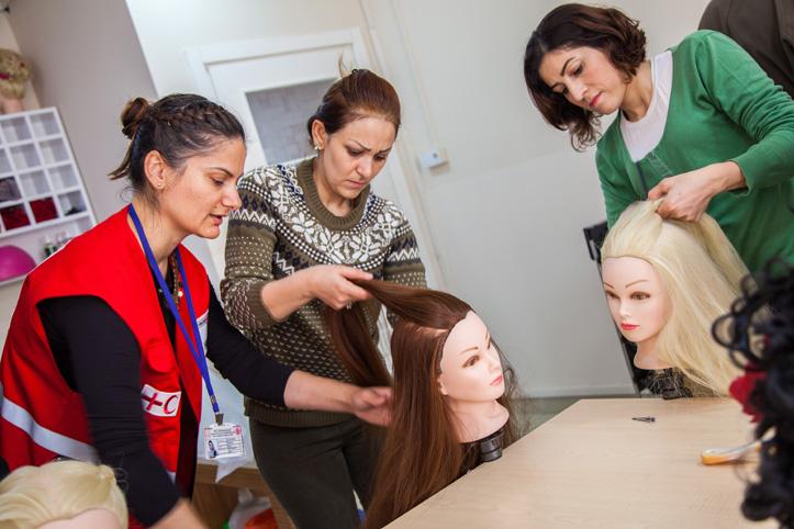 Foto: Rothalbmond-Mitarbeiterin beobachtet zwei die Arbeit zweier Frisierkursteilnehmerinnen