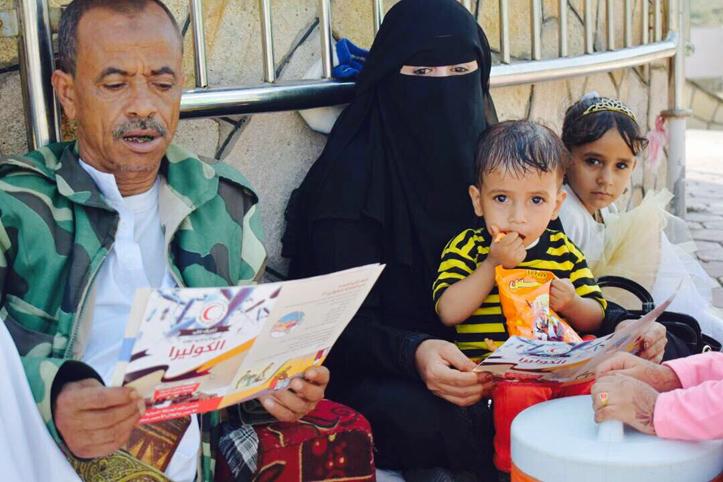 Foto: Jeminitischer Familienvater neben seiner Familie liest Aufklärungsbroschüre