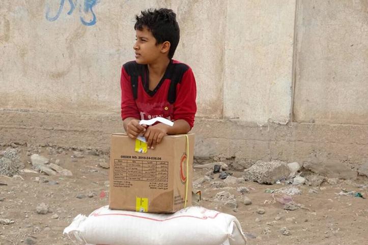 Foto: Jemenitischer Junge lehnt sich auf eine Kiste mit Hilfsgütern