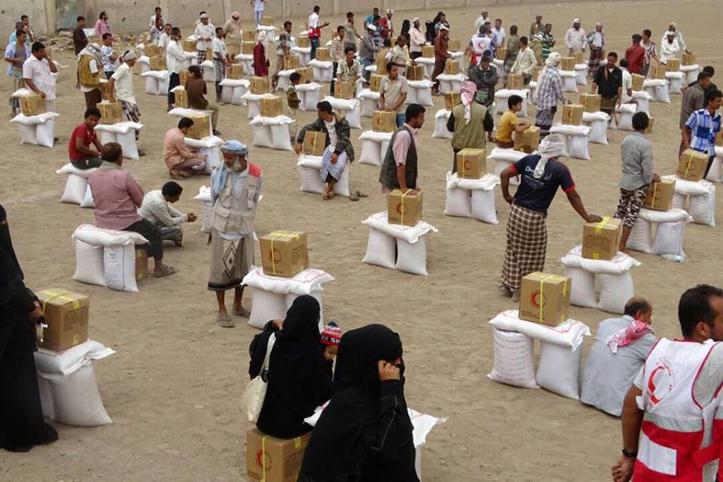Foto: Platz mit aufgereihten Hilfsgütern und Menschen daneben