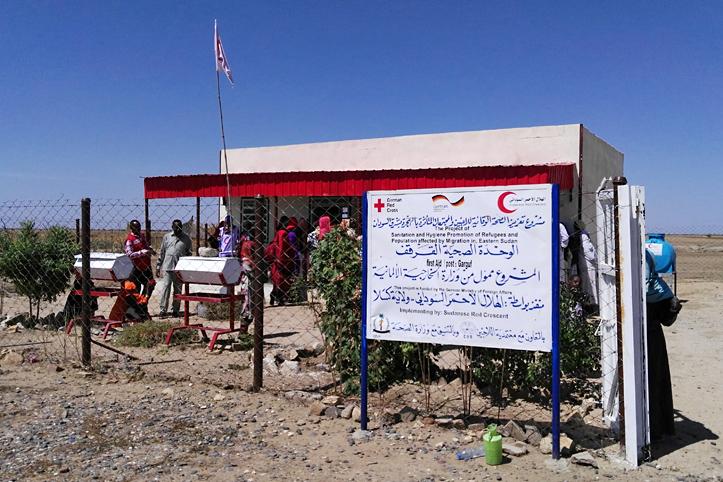 Foto: Blick auf die Erste-Hilfe-Station in Garguf, davor ein Schild mit DRK-Logo